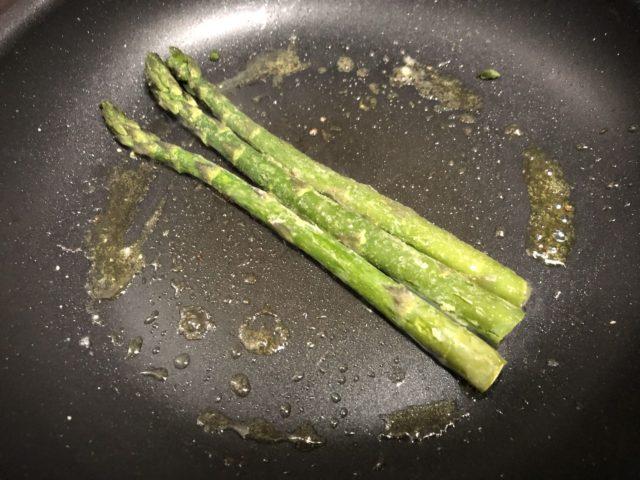 アスパラを炒め、目玉焼きを作る